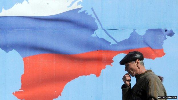 Man walks past poster of Crimea with colours of the Russian flag in Simferopol on 13 March 2014