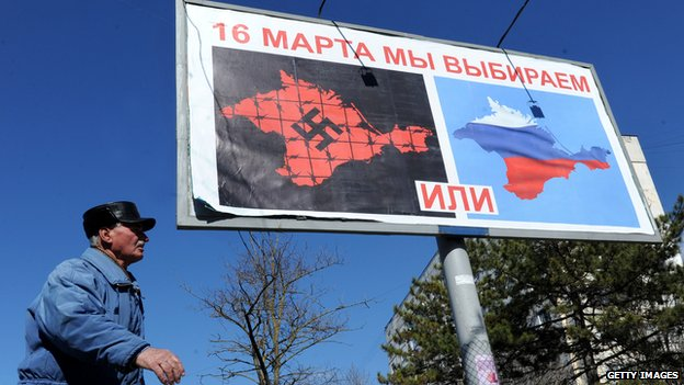 A man walks past a poster in Sevastopol reading 'On March 16 we will choose either... or...' and depicting Crimea in red with a swastika and covered in barbed wire (L) and Crimea with the colours of the Russian flag.