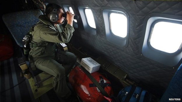 A member of the Malaysian air force looks out over the Straits of Malacca during the search operation