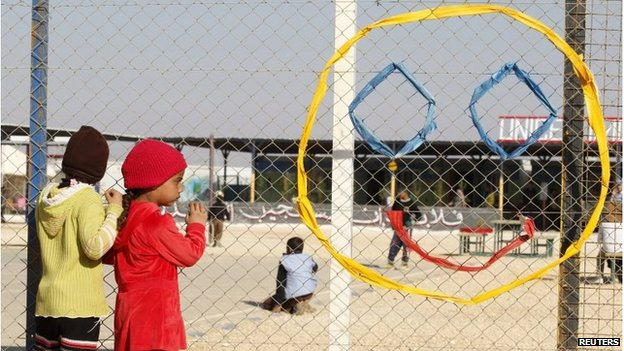 Syrian children stand in front of a UNICEF centre with a smiley face woven into the fence in front of them