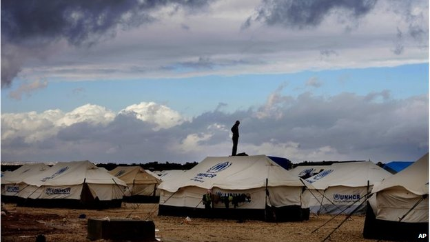 A Syrian refugee stands on top of a water tank behind a tent at the Zaatari refugee camp
