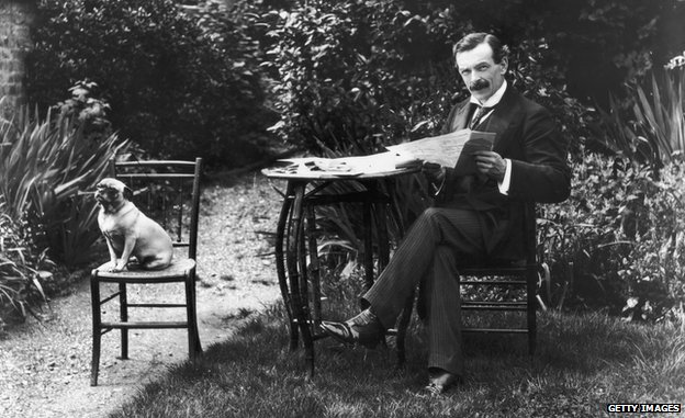 Welsh Liberal politician and future Prime Minister David Lloyd George (1863 - 1945) enjoys a quiet read of a newspaper in his garden with his faithful dog for company