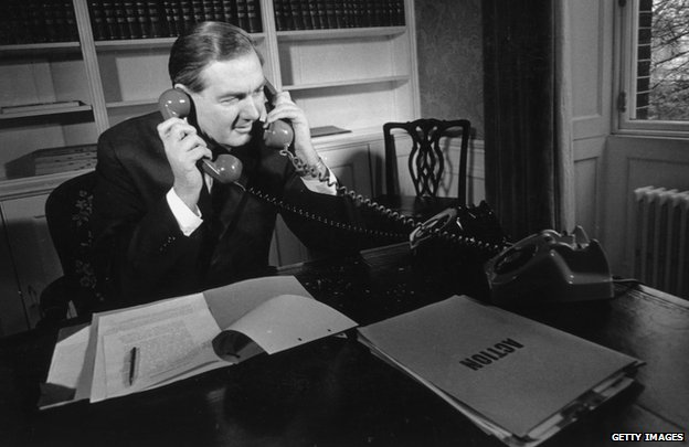 Sitting in his office, Chancellor of the Exchequer in the Labour government, James Callaghan answers two phones at once, on his desk a file marked 'Action' in large letters.