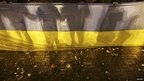 Participants of an anti-war rally hold a national flag as eggs thrown by pro-Russia protesters cover the floor during their clashes in Donetsk