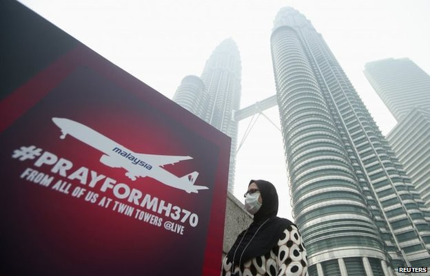 "A woman wearing a mask against the haze walks past a board saying ""Pray for MH370"" in Kuala Lumpur, March 14"