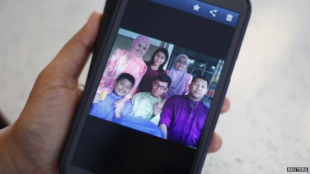 Arni Marlina, 36, a family member of a passenger onboard the missing Malaysia Airlines flight MH370, shows a family picture on her mobile phone, at a hotel in Putrajaya 9 March 2014. Marlina's stepbrother Muhammad Razahan Zamani (bottom, right), 24, and his wife Norli Akmar Hamid, 33, were on their honeymoon on the missing flight