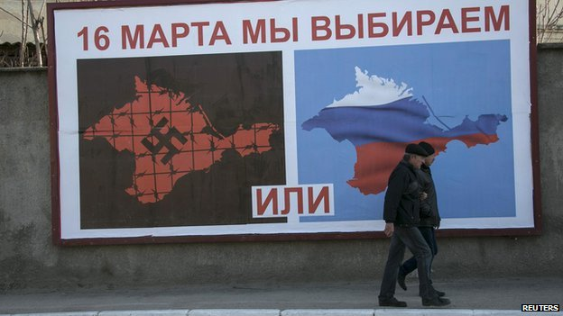 Men walk past a poster calling people to vote in the upcoming referendum, at the Crimean port of Sevastopol on 14 March 2014.