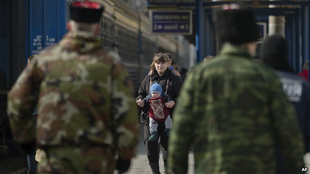 A woman walks with a baby as members of the Crimean self defence forces stand on the platform at the main railway station in Simferopol, Ukraine, on 14 March 2014.