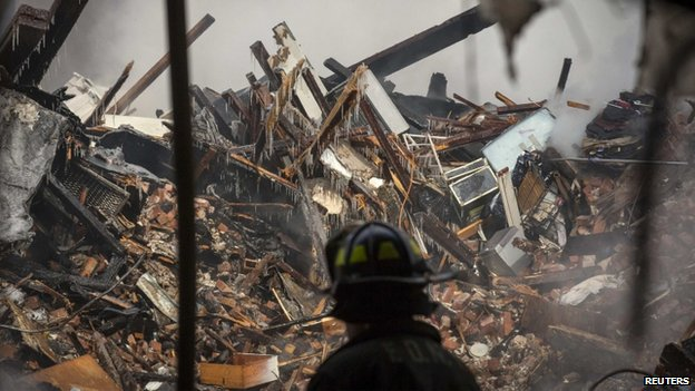 A New York City firefighter looks at the rubble at the site of a building explosion in New York City on 13 March 2014