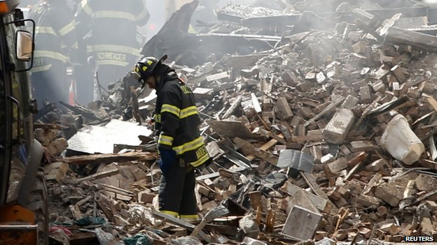 New York City emergency responders search through the rubble at the site of a building explosion in New York City on 13 March 2014