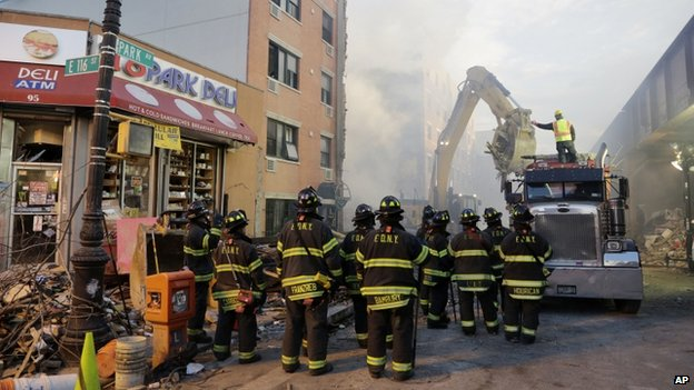 An bulldozer removes debris from the site of a building explosion in New York City on 13 March 2014