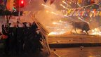 Riot policemen shield themselves as fireworks thrown by protesters explode next to the statue of a bull