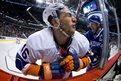 New York Islanders' Matt Donovan is checked into the glass by Vancouver Canucks' Henrik Sedin