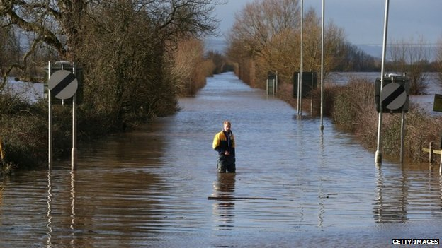A man stands in floodwater at the A361 at Burrowbridge on the Somerset Levels on February 10