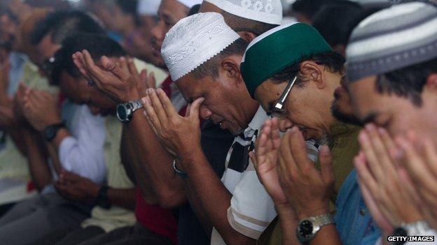 People pray in Kuala Lumpur, Malaysia. Photo: 14 March 2014