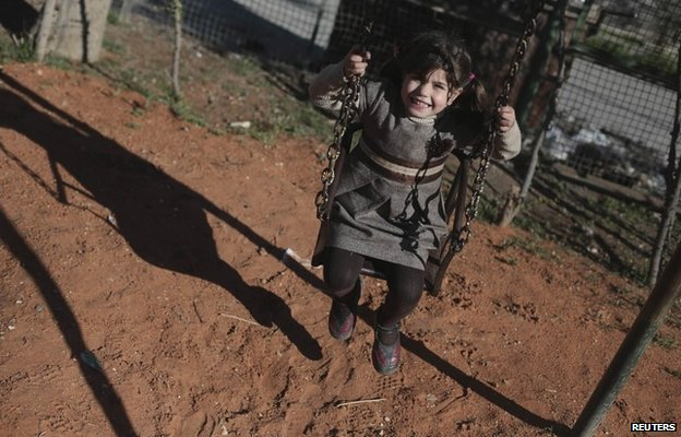 A three-year-old girl plays on a swing in the Douma district of Damascus (10 March 2014)
