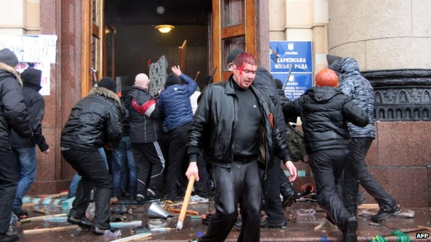 An injured man carries a club as pro-Russian activists clash with pro-Ukrainian supporters in Kharkiv. Photo: 1 March 2014