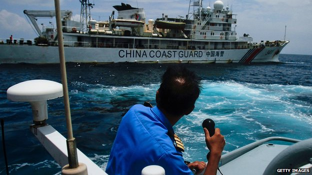 Member of Malaysia Navy makes a call as a Chinese Coast Guard ship passes close by in Kuantan, Malaysia, on 15 March 2014