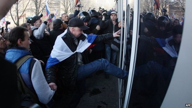 Pro-Russian activists try to storm into Ukraine's Security Service building following a rally in the eastern Ukrainian city of Donetsk on March 15