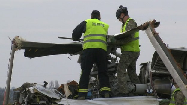 Crews work to removed rotor blades from the crashed AW139