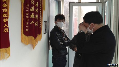 Friends of human right activist Cao Shunli stand in front of an intensive care unit where Cao is hospitalized as they are not allowed to go inside of the unit at a hospital in Beijing (1 March 2014)