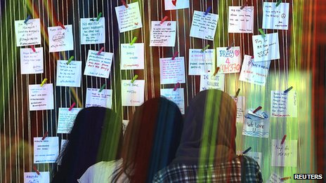 Women look at messages for family members of passengers onboard the missing Malaysia Airlines Flight MH370 at an event to express solidarity in Subang Jaya