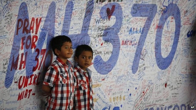 Two Malaysian children stand in front of messages board and well wishes to people involved with the missing Malaysia Airlines jetliner MH370