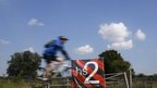 A man cycles past an anti high speed rail project (HS2) banner in Austrey, central England