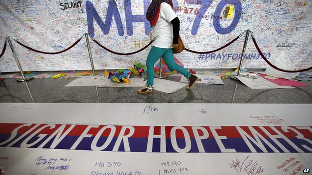 A woman walks past a banner filled with messages of hope for the missing Malaysia Airlines jetliner MH370 at Kuala Lumpur International Airport