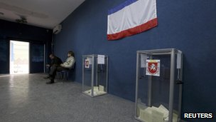 Officials wait for voters inside a polling station in Bakhchisaray