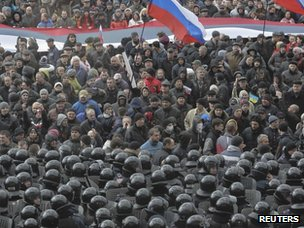 Riot police stand guard in front of a regional government building as pro-Russian demonstrators take part in a rally in Kharkiv