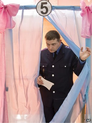 A policeman exits a voting booth after casting his vote in the village of Perevalne, southern Ukraine