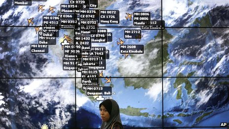 A lady stands in front of an electronic display showing live information of flight positions according to predicted time and flight duration calculations at the Kuala Lumpur International Airport