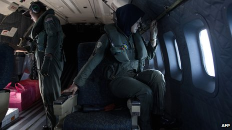 Malaysian air force crew members work during a search-and-rescue operation to find the missing Malaysia Airlines flight MH370 plane over the Strait of Malacca on 15 March 2014