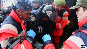 Rescue workers carry a wounded policeman in Donetsk on 16 March 2014