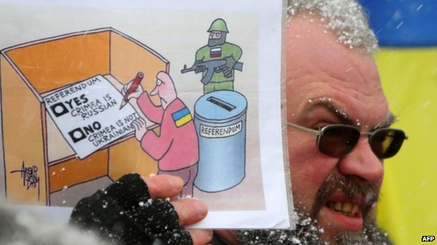 A demonstrator holds a comic drawing featuring the Crimea referendum during a protest in Vilnius, Lithuania. Photo: 16 March 2014