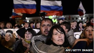People sing the Russian national anthem as they celebrate in Simferopol's Lenin Square