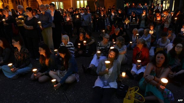 People attend a candlelight vigil in support of asylum seekers, in Sydney on 23 February 2014