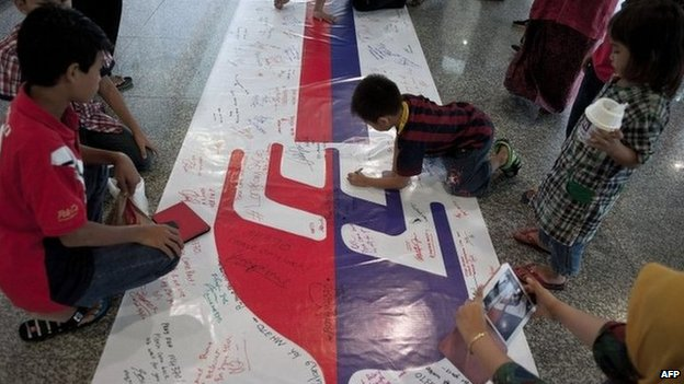 Visitors write on a banner carrying messages for the passengers of missing Malaysia Airlines flight MH370 at Kuala Lumpur International Airport (KLIA) in Sepang, outside Kuala Lumpur on 16 March 2014