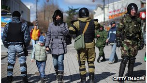 Members of the public walk between a line of Russian and Ukrainian Berkut riot police