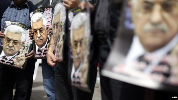 Fatah supporters hold posters showing pictures of President Mahmoud Abbas at a rally in the West Bank city of Ramallah (17 March 2014)