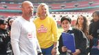 Robbie Savage and Alan Shearer standing pitch-side with the School Reporters