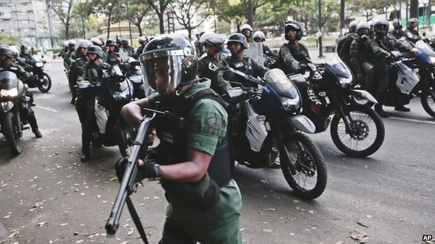 A Bolivarian National Guard aims his weapon while searching for anti-government demonstrators after they dispersed from Plaza Altamira in Caracas on 16 March, 2014