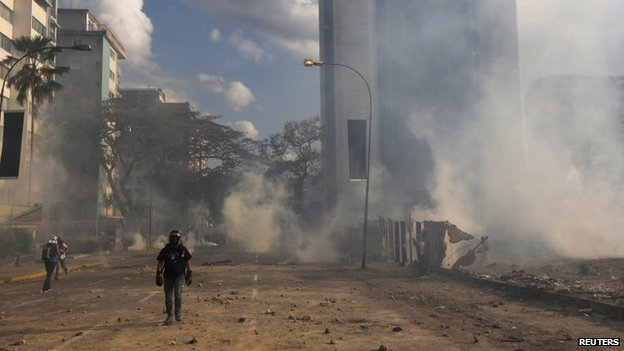 Anti-government protesters walk amidst teargas during a protest against Nicolas Maduro's government at Altamira square in Caracas on 16 March, 2014
