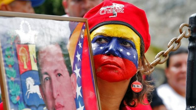 Handout photo released by the Venezuelan Presidency of a supporter of Venezuelan President Nicolas Maduro holding a portrait of late Venezuelan President Hugo Chavez during a rally at the presidential palace in Caracas on 16 March, 2014