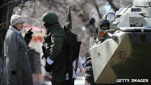 An elderly woman speaks to a Russian military man outside a Ukrainian military base on March 17, 2014