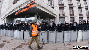 A pro-Russian activist holds a flag during a rally as police forces stand guard