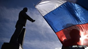 "A man waves Russian flags in Simferopol""s Lenin Square"