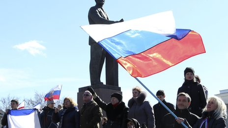 Participants in a pro-Russian rally wave Russian flags in front of a statue of Soviet state founder Vladimir Lenin in Simferopol on 17 March 2014.