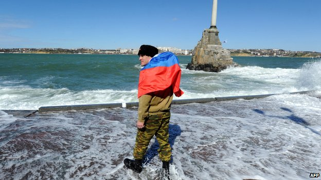 Pro-Russian self-defence activist wearing a Russian flag as he walks on Sevastopol embankment on 17 March 2014.